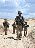 Patroling the desert. Squad of soldiers patrolling across the desert Royalty Free Stock Image
