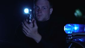 Patrolman getting out of car and aiming pistol at perpetrator, law and order. Stock footage stock video footage