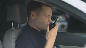 Patrolman transmitting information using two-way radio, waiting for instructions