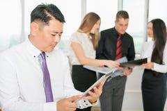 Patron asiatique exécutif à l'aide du PC de comprimé avec son équipe d'affaires Images libres de droits