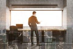Patron avec un téléphone dans son bureau, modifié la tonalité Photo stock