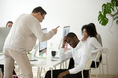 Patron blanc fâché grondant réprimandant l'employé noir incompétent dedans photo stock