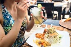 Patron de femme mangeant des fruits de mer et buvant le cocktail dans le restaurant Photographie stock
