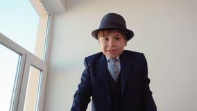 Patron de garçon dans l'entretien classique de costume et de chapeau à la caméra banque de vidéos