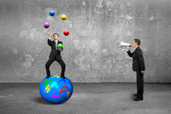 Patron employant l'homme d'affaires de hurlement de haut-parleur équilibrant sur le juggl de sphère Images stock