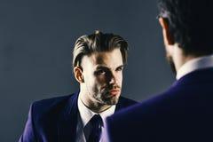 Patron et employé parlant lors de la réunion sur le fond foncé Homme dans la veste écoutant son associé avec concentré Images stock