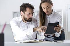 Patron et secrétaire regardant la calculatrice Photographie stock libre de droits