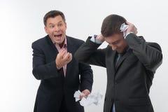 Patron fâché avec le jeune employé Image stock