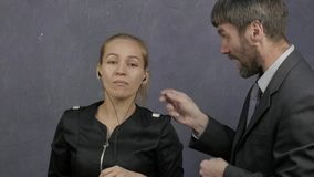 Patron fâché grondant le jeune employé pour le mauvais résultat fille indifférente écoutant la musique sur des écouteurs 4K clips vidéos