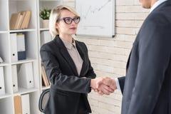 Patron féminin Shaking Hands avec l'associé photo stock