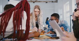Patron femelle blond positif de société collaborant avec les collègues multi-ethniques, travail d'équipe sur le lieu de travail s banque de vidéos