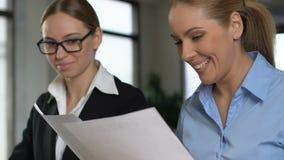 Patron femelle satisfait regardant par des documents de travail, préparés par le collègue clips vidéos