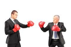 Patron mûr fâché et jeune homme d'affaires avec les gants de boxe rouges Photos stock