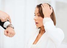 Patron montrant le temps à la femme d'affaires soumise à une contrainte Photo stock
