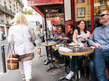 Patrons laughing at cafe tables near Saint Germain, Paris. Paris, France, Sept 5, 2015: Patrons laugh and drink red wine at Saint Germain cafe Royalty Free Stock Photography