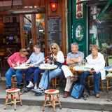 Patrons Relaxing at a Montmartre Cafe. PARIS, FRANCE - JUNE 6, 2012: Unidentified patrons relaxing and enjoying a drink at a cafe in Montmartre in Paris Stock Image