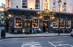 Patrons socialize at tables outside Museum Tavern, London. London, England, August 20, 2015: Patrons socialize at tables outside the Museum Tavern, Bloomsbury Royalty Free Stock Photo