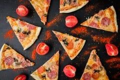Patroon met Italiaanse pizza met ingrediënten Vlak leg, het patroon van Pizzaspaanders op donkere lijst stock afbeelding