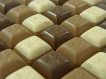 Patroon van dark, melk en witte chocoladestukken Stock Afbeeldingen