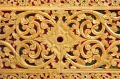 Patroon van gouden die bloem op de achtergrond van de steenmuur wordt gesneden Royalty-vrije Stock Afbeeldingen