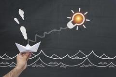 Patroszona Elektryczna żarówka z wody i busunessman ` s ręki mienia origami Tapetuje łódź zdjęcia stock