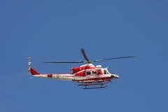 Patrouillez l'hélicoptère des sapeurs-pompiers en ciel bleu au-dessus d'un feu Images libres de droits