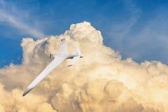 Patrullar los aviones sin tripulación en el cielo contra el contexto de las nubes potentes de la tempestad de truenos imagenes de archivo