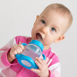 Patrycja with a bottle. Adorable baby girl drinking water from the bottle Royalty Free Stock Photos