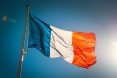Patrzeć do pięknej falowanie francuza flagi przeciw niebieskiemu niebu obrazy royalty free