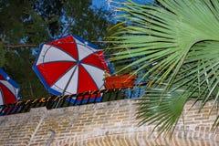 Patrzeć do zabawnego patia na górze ściana z cegieł przy nocą z smyczkowymi światłami, parasole i palmowi fronds obrazy stock