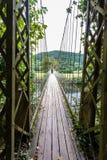 Patrzeć wzdłuż drewnianego zawieszenie mosta przejścia fotografia royalty free