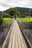 Patrzeć wzdłuż drewnianego zawieszenie mosta przejścia obrazy stock