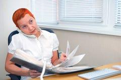 Patrzejący przez dokumentów dziewczyna biurowy kierownik opowiada na telefonie zdjęcie stock