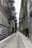 Patrzejący w dół miasto alei drogę z graffiti na ściana ceglanych brukarzy rocznika starej ulicie miastowy miasta położenie Obrazy Stock