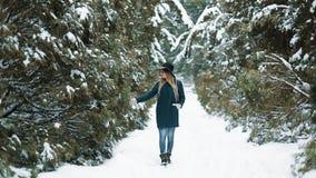 Patrzeje od behind przy damą w zielonym kapeluszu i żakieta odprowadzeniem wokoło zima lasu dziewczyn pozy na kamerze i spojrzeni zbiory