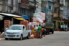 Men unloading goods onto a trolley on road side market bazaar Pattani Thailand royalty free stock photo