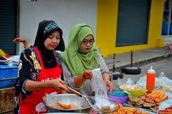 Muslim Thai women cook at street stall at food street bazaar Pattani Thailand stock photography
