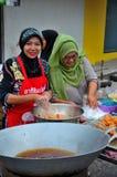 Muslim Thai women cook at street stall at food street bazaar Pattani Thailand royalty free stock images