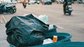 Pattaya, Tailândia - 16 de dezembro de 2017: A lata de lixo completa com os grandes sacos de lixo completamente do alimento e do  video estoque