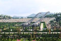 PATTAYA, TAIL?NDIA - 24 DE ABRIL DE 2019: Vale gigante do dinossauro da visita do turista no jardim de Nong Nooch fotografia de stock