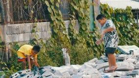 PATTAYA, TAILÂNDIA - 16 de dezembro de 2017: Crianças do mendigo de um tijolo pobre e de pedras do recolhimento nas ruas da cidad filme