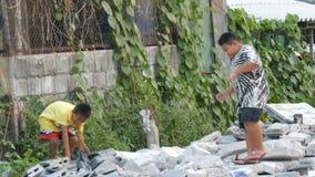 PATTAYA, TAILÂNDIA - 16 de dezembro de 2017: Crianças do mendigo de um tijolo pobre e de pedras do recolhimento nas ruas da cidad video estoque
