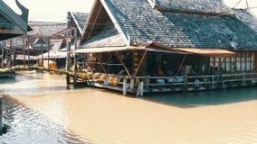 PATTAYA, TAILÂNDIA - 18 de dezembro de 2017: Uma casa de madeira que está em um rio da cor marrom Casa na água em Tailândia, sobr filme