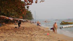 PATTAYA, TAILÂNDIA - 4 DE FEVEREIRO DE 2017: Os povos estão sentando-se na praia antes do por do sol Os turistas estão descansand filme