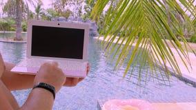 Pattaya Tajlandia, Maj, - 15, 2019: Męski działanie na jego laptopie, siedzi basenem Samiec ręki na klawiaturze w zbiory wideo