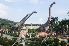 PATTAYA THAILAND - APRIL 24, 2019: J?tte- dinosauriedal f?r turist- bes?k p? den Nong Nooch tr?dg?rden royaltyfria foton