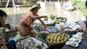 Asian salesman on small boat with fruits and vegetables sells the goods. Pattaya Floating Market. PATTAYA, THAILAND, DECEMBER 16, 2017: Asian male salesman on a stock video