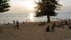 People are resting on the tropical beach at sunset. Pattaya, Thailand. PATTAYA, THAILAND, DECEMBER 14, 2017: People are resting on the tropical beach at sunset stock video footage