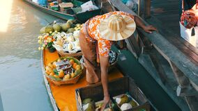 Pattaya, Thailand - December 18, 2017: The seller of exotic fruits on a boat and a straw hat sails on the river in. Thailand, on a floating market, Pattaya stock footage