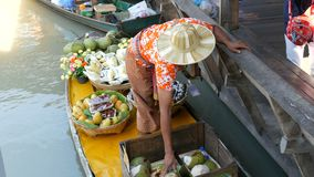 Pattaya, Thailand - December 18, 2017: The seller of exotic fruits on a boat and a straw hat sails on the river in. Thailand, on a floating market, Pattaya stock video footage